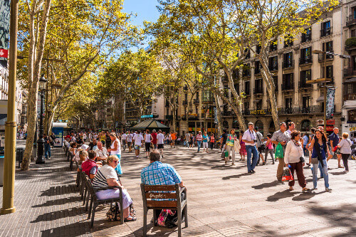 People at the La Rambla street with the Liceu Theater at the heart of Barcelona, Spain