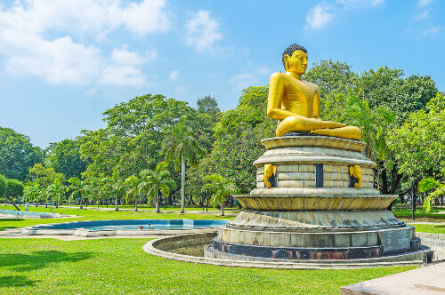 The giant golden statue of Buddha decorates the central alley of Viharamahadevi formerly Victoria park in Colombo, Sri Lanka
