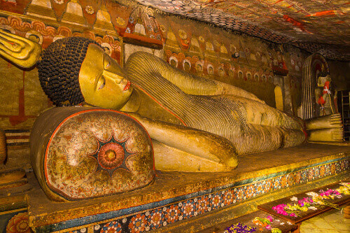 A statue of reclining Buddha in the ancient Buddhist cave temple at Dambulla in Sri Lanka