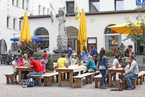 A lot of tourists daily gather on a small square in front of the Municipal House in St Moritz Switzerland