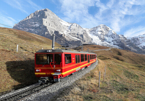 A cog wheel train travels on Jungfrau Railway from Jungfraujoch  to Kleine Scheidegg in Bernese Oberland Switzerland