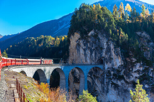 The train of Rhaetian Railway running on the famous Landwasser Viaduct into the tunnel of Canton of Grisons in Switzerland