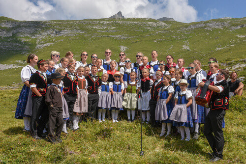 People wearing traditional swiss clothes yodelling at Engstlenalp on the Swiss alps in Switzerland