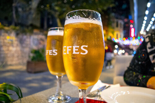 Tourists drinking Efes Beer in the Sultanahmet district of Istanbul Turkey