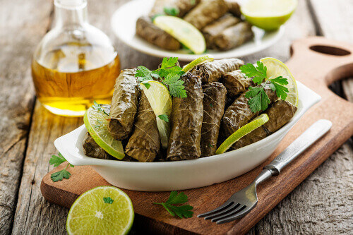 Traditional turkish dish called Dolma with stuffed grape leaves with rice and meat on wooden background