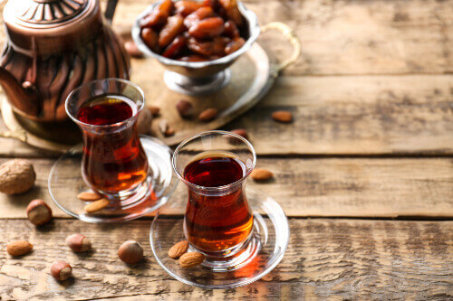 Turkish tea in traditional glasses with nuts on wooden background
