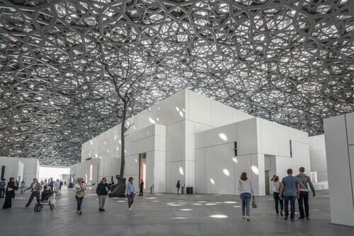 "Interior of the Louvre Museum showing reflections of the ""Rain of Light"" dome in Abu Dhabi United Arab Emirates"