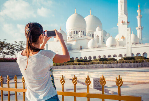 Woman shooting on a phone at Sheikh Zayed great white mosque in Abu Dhabi United Arab Emirates