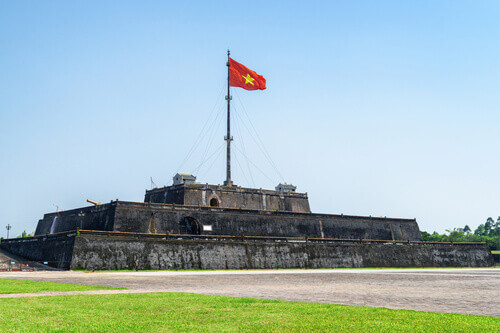 Wonderful view of the flag of Vietnam fluttering over a tower of the Citadel on blue sky background in Hue Vietnam