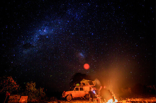 Camping at night with fire and stars in the Hwange National Park in Zimbabwe