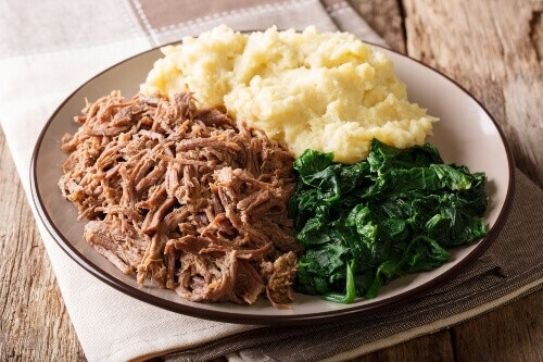 Zimbabwean meal consisting of stewed beef with pap porridge and spinach