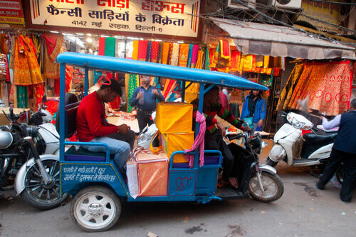 rickshaw in front of clothing stall chandni chowk delhi india
