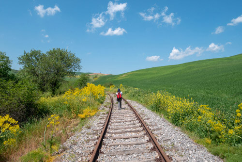 person walking through countryside italy