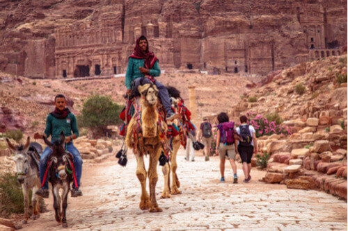bedouin men riding camels in petra jordan