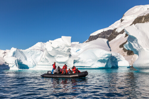 people in zodiac in icy antarctic water