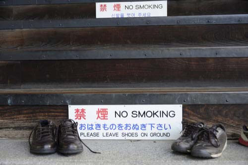 leave shoes on ground sign outside temple japan