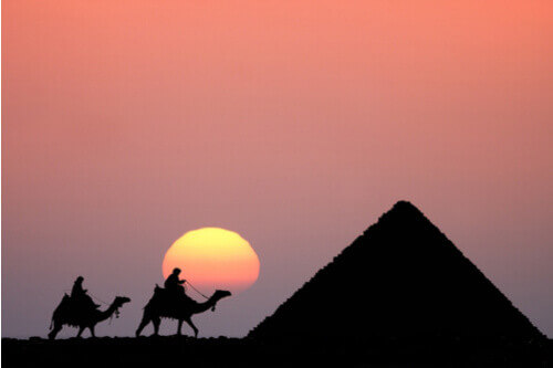 two people riding camels in front of pyramid sunset egypt