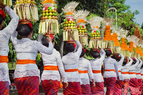Balinese women in traditional costumes - sarong, carry offering on heads for Hindu ceremony