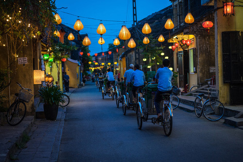 people cycling through hoi an lantern streets vietnam