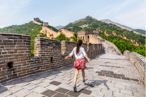 woman walking great wall with arms wide