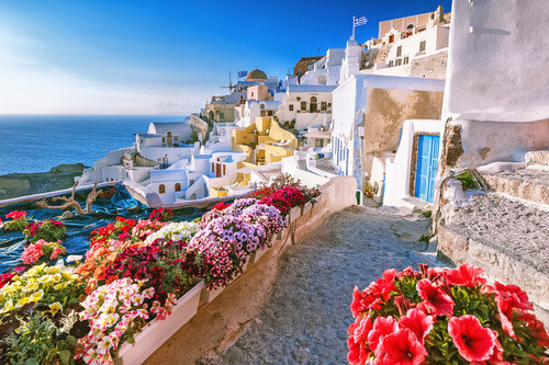 streets of santorini with caldera, whitewashed buildings and flowers greece