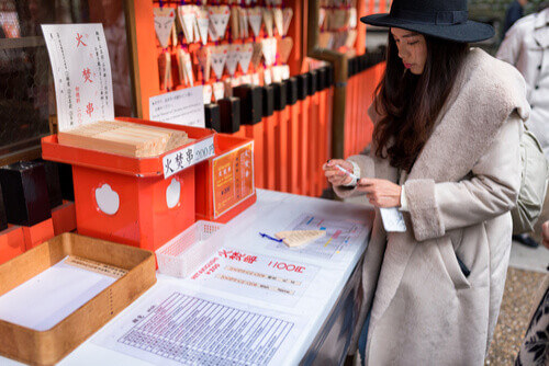 woman writing fortune on fox ema plaque kyoto japan
