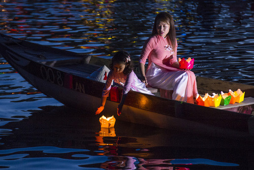 vietnamese girl releasing lantern into river hoi an vietnam