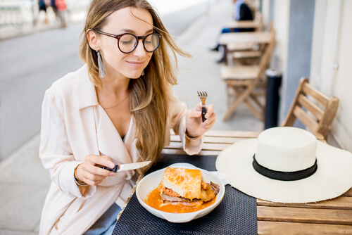 Woman eating Francesinha Sandwich Porto Portugal