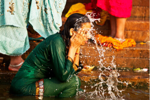Woman washing face in ganges